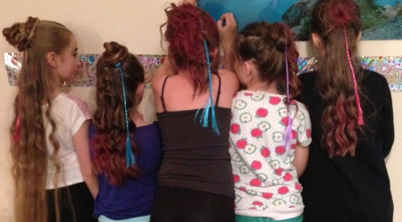 Hair styling with spray and party hair pieces.